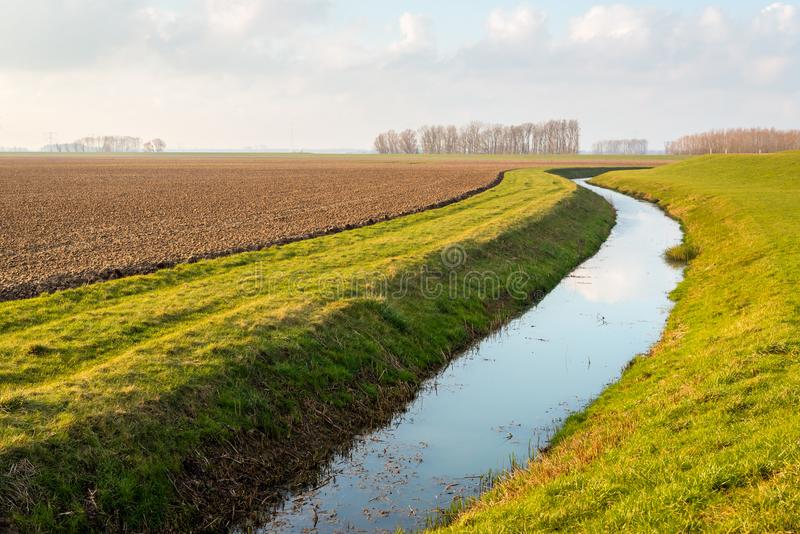 Water surface of a meandering ditch reflects the white clouds in royalty free stock image