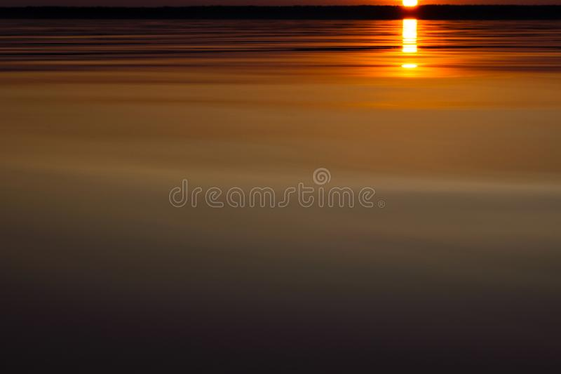 Water surface. View of a Sunset sky background. Dramatic gold sunset sky with evening sky clouds over the sea. View of a Crystal c stock images