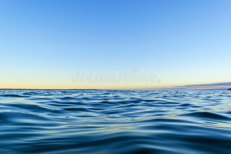 Water surface. View of a Sunset sky background. Dramatic gold sunset sky with evening sky clouds over the sea. View of a Crystal c stock image