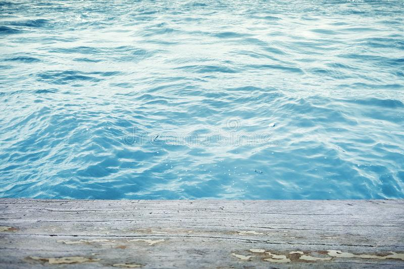 Water surface with wooden table in front stock photography