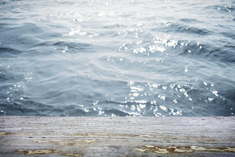 Water surface with wooden table in front royalty free stock image