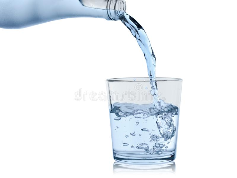 Water from the sweating bottle is poured in a glass glass, isolated on a white background.  royalty free stock images