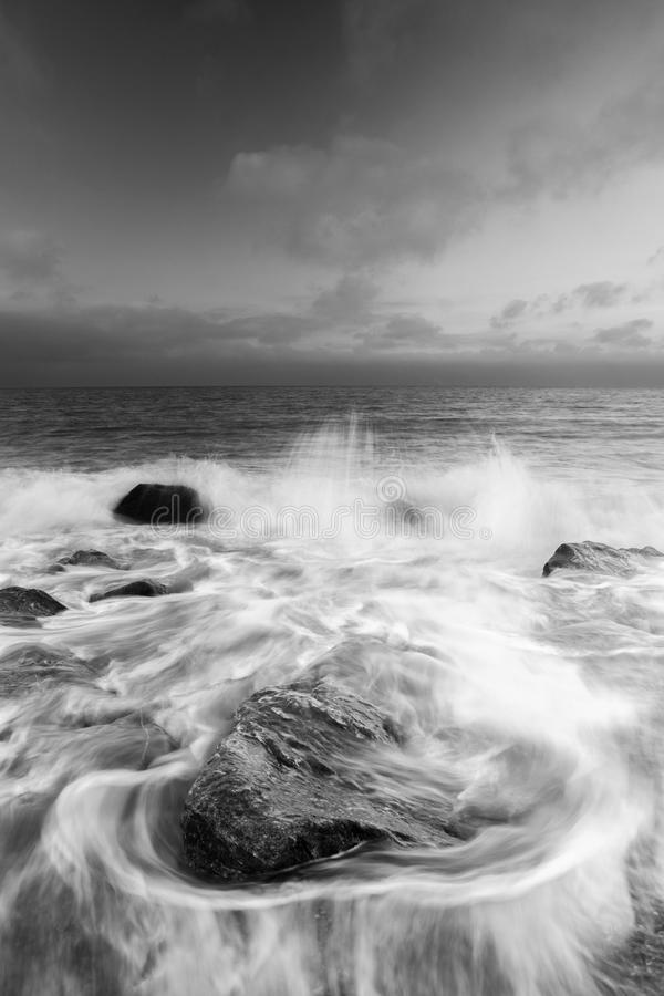 Water swirling around rocks in the sea stock images
