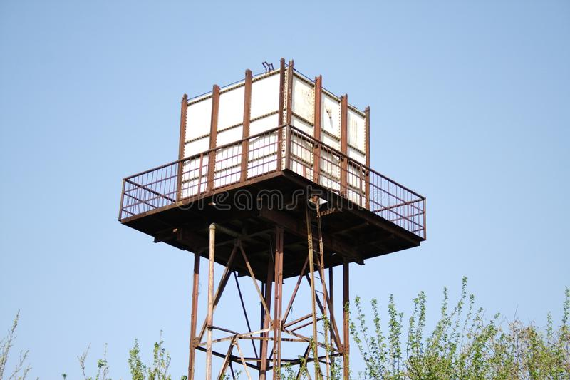 Water tank. An old overhead water tank is well supported by a structure and is accessible via a well made railing royalty free stock photography