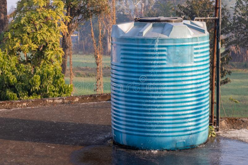 Water tank overflowing, fitted in house. Water tank overflowing, wasting water stock image