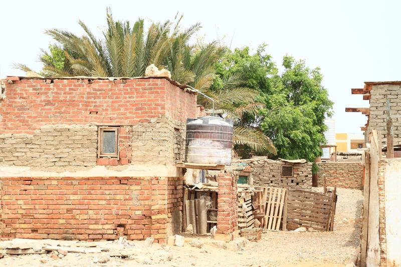 Water tank behind poor house in Marsa Alam. Water tank in poor house made from bricks with trees behind in desert in Marsa Alam, Egypt, Africa stock photo