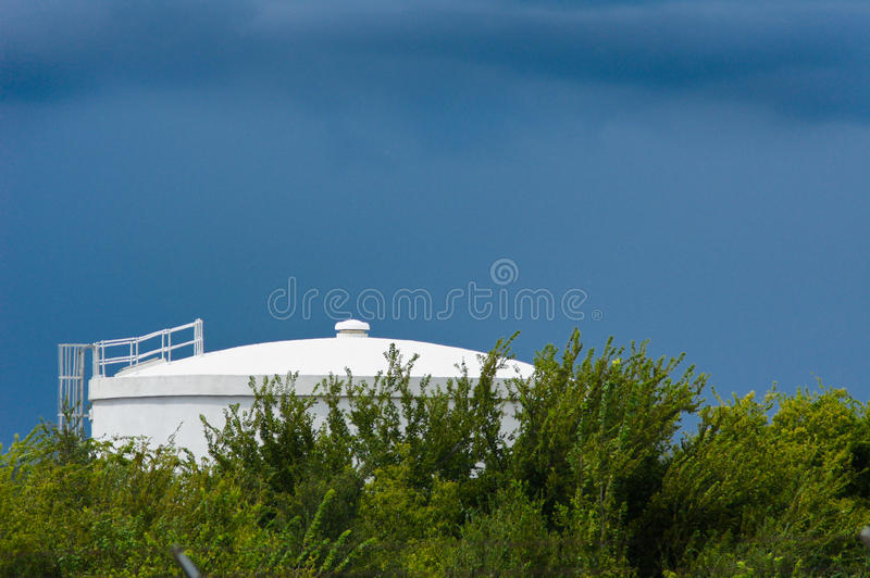 Water tank. Under blue skies, clouds and green brush stock photography