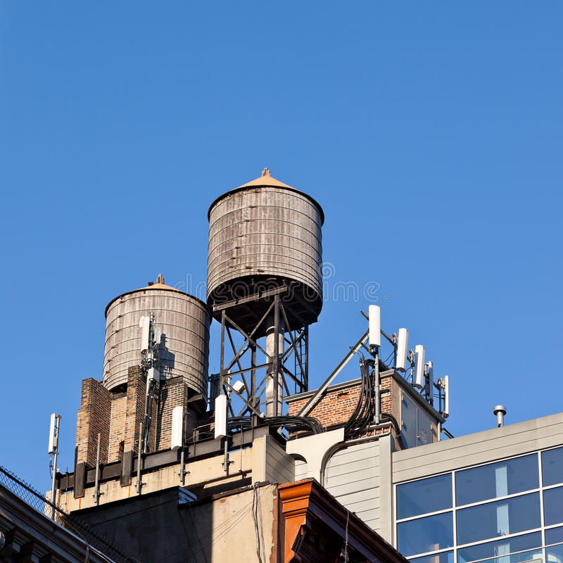 Water tanks and cell phone receivers. On top of a building in New York City royalty free stock photo