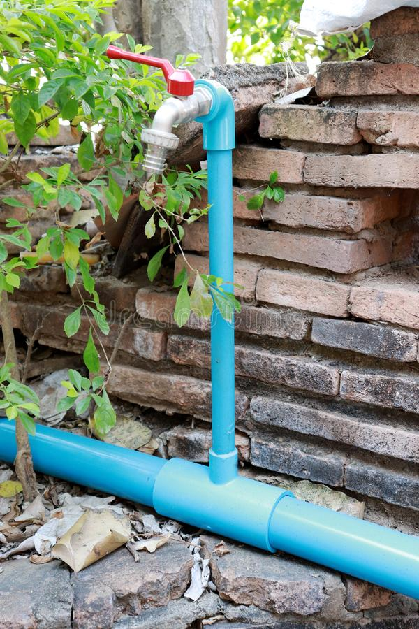 Water tap. Blue tube faucet and the red shutter valve stock photography