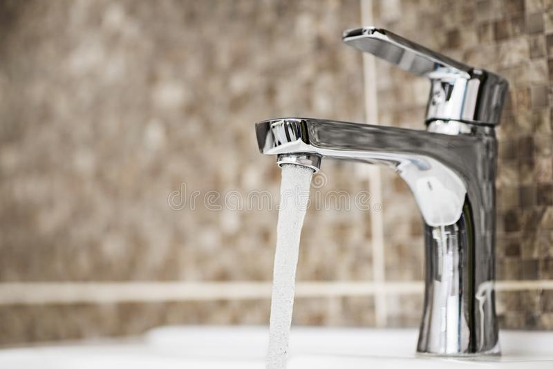 Water tap flowing in the bathroom. Open chrome faucet washbasin stock image