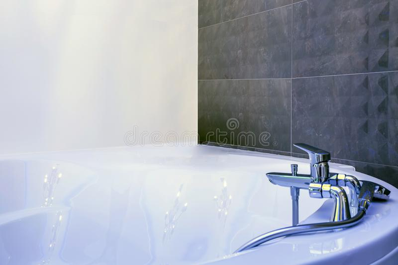 Water tap sink with faucet detail of jacuzzi with wall mount shower attachment royalty free stock photography