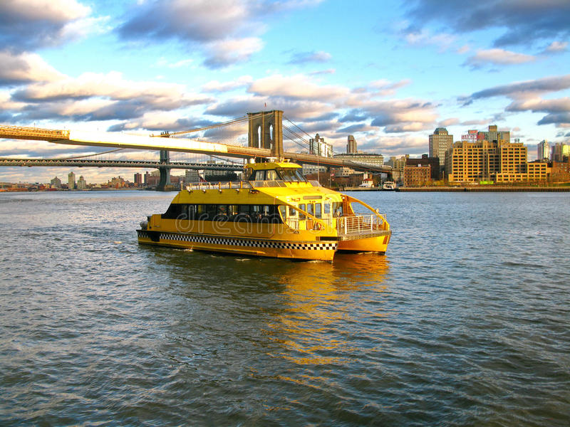Water Taxi and Brooklyn bridge, seen from Pier 17, at Lower Manhattan in New York. South Street Seaport is a historic area of Man royalty free stock photos
