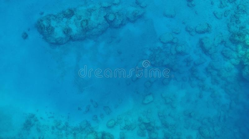 Water texture in ocean with corals. Blue sea water texture aerial drone view. Blue lagoon water surface royalty free stock image