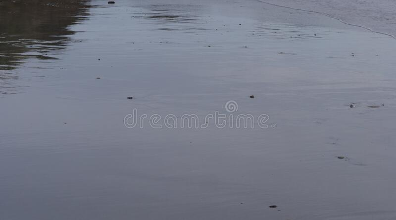 Water textures and reflections on a cold winters day at the beach,. Sea, ocean textures of moving water, in a quiet moment of storm Dennis,  waves reaching a royalty free stock photos