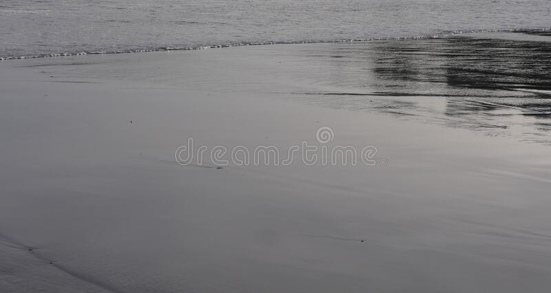 Water textures and reflections on a cold winters day at the beach,. Sea, ocean textures of moving water, in a quiet moment of storm Dennis,  waves reaching a royalty free stock photo