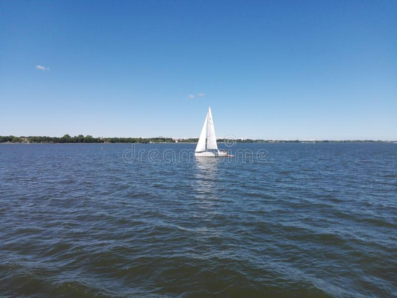 Water touch the sky and a sailboat royalty free stock photos