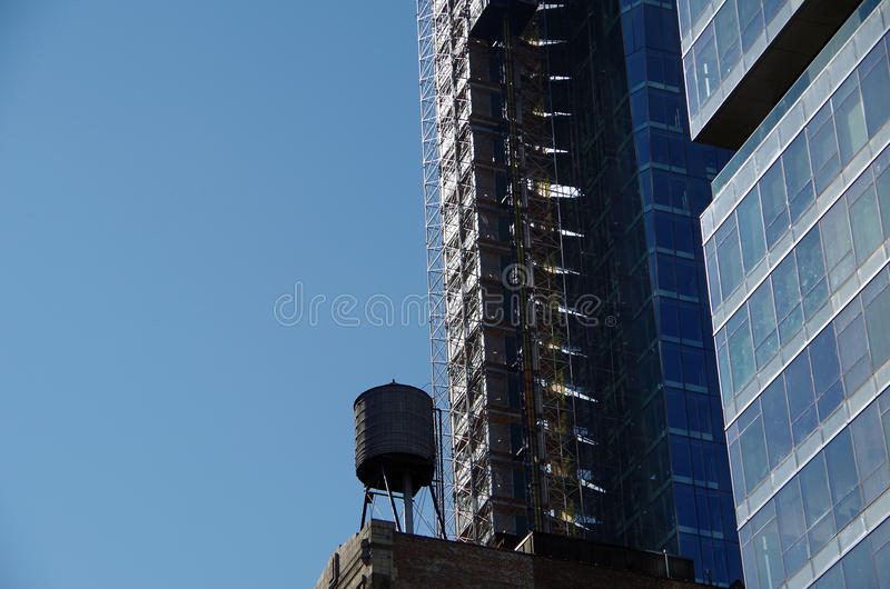 Water tower against blue sky. Water tower on roof top in NYC royalty free stock images