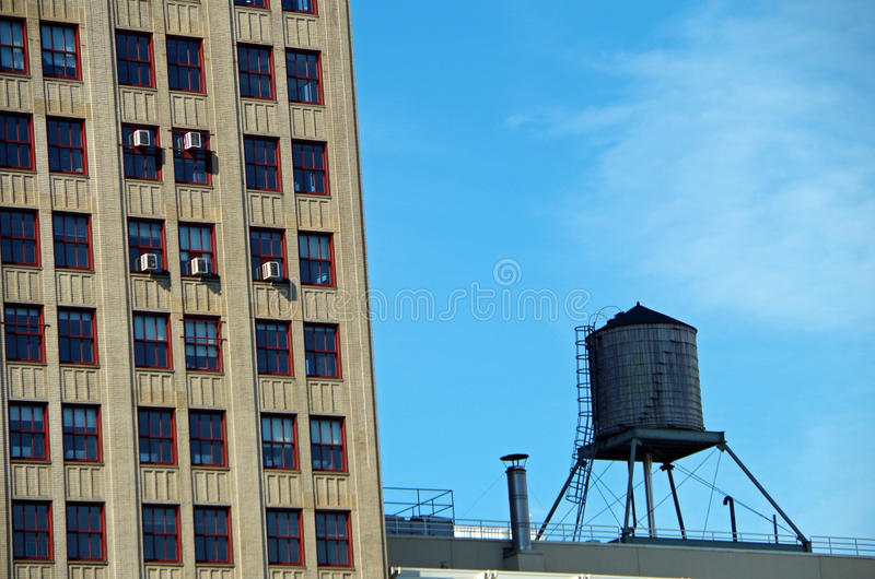 Water tower and high-rise building. With blue sky in NYC royalty free stock photography