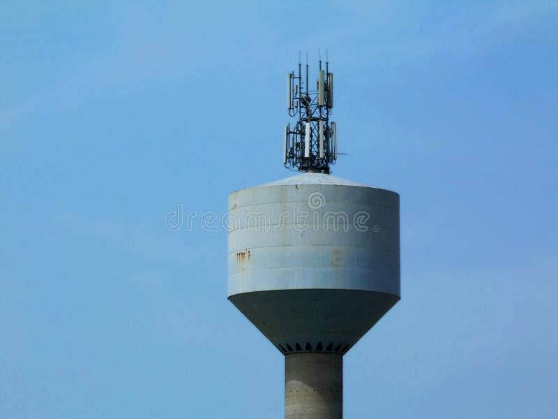 Water tower with telecommunication transmitter tower royalty free stock photos