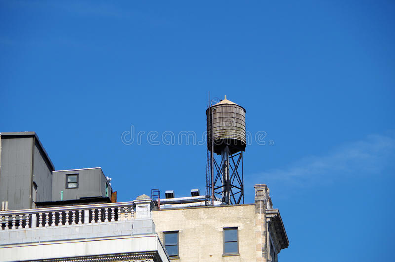 Water tower with urban sky. Water tower in NYC with blue skies stock image