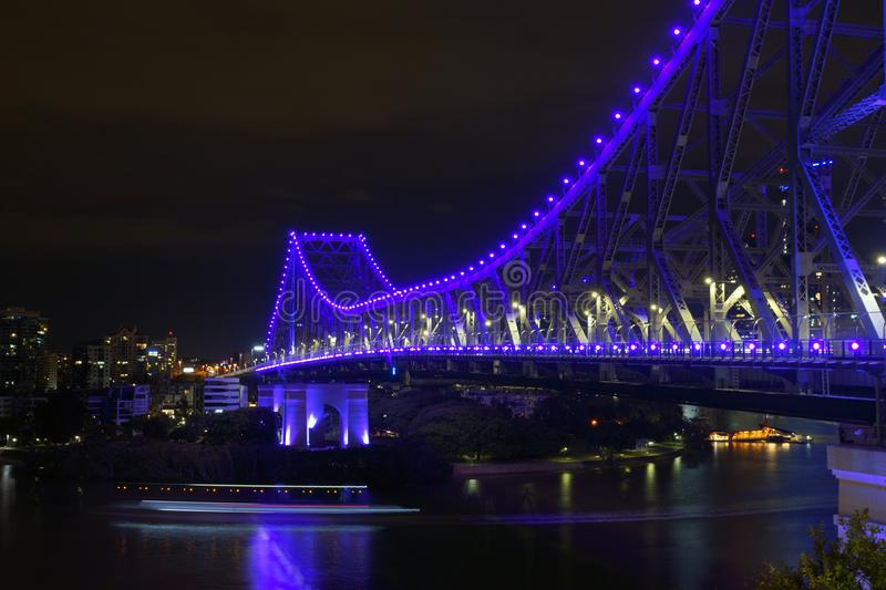 Water traffic by night under blue light bridge. Blurred water traffic light motions on river at night time with illuminated blue bridge lights above in Brisbane stock image