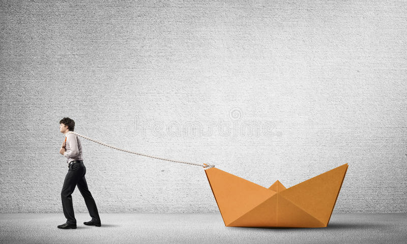 Water transporation concept. Successful businessman pulling with rope paper boat royalty free stock photos