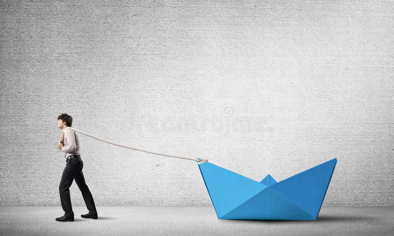 Water transporation concept. Successful businessman pulling with rope paper boat stock image