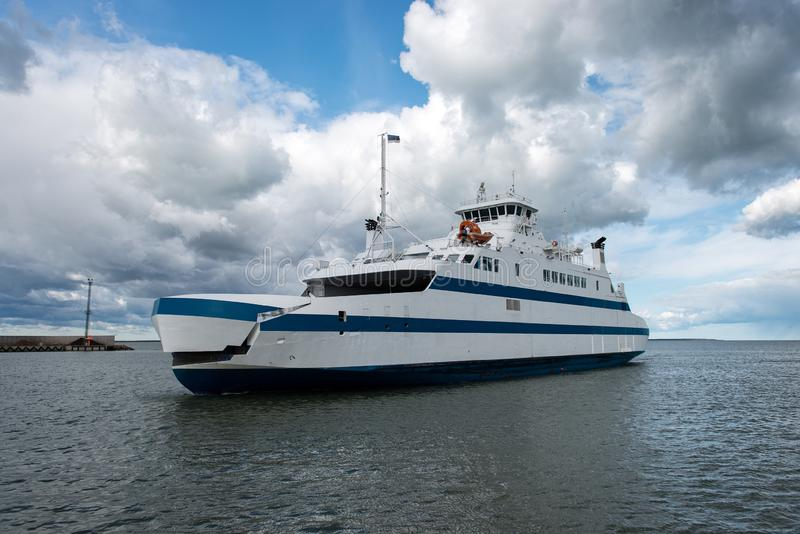 Water transport. Sunny day white ferry arrives quay.  stock image