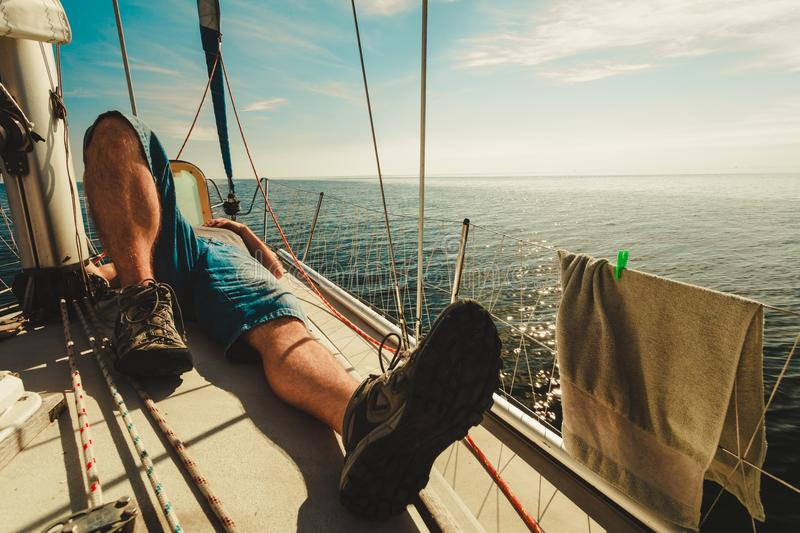 Man relaxing on sport yacht front. Water traveling, adventure concept. Man relaxing lying on sporty yacht front, blue calm water, sunny weather, sky with white royalty free stock photography