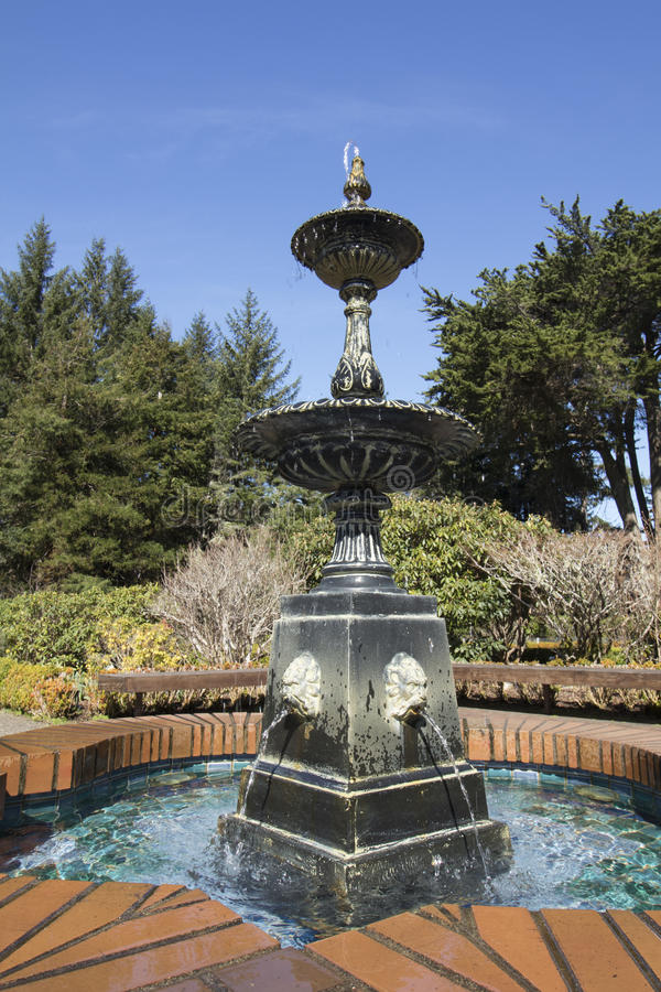 Water trickling over a fountain on a sunny day at Shore Acres State Park, Oregon stock image