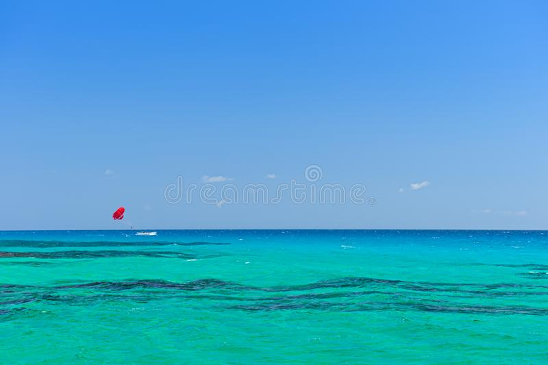 Turquoise sea with a boat and a red parachute. Parasailing stock image