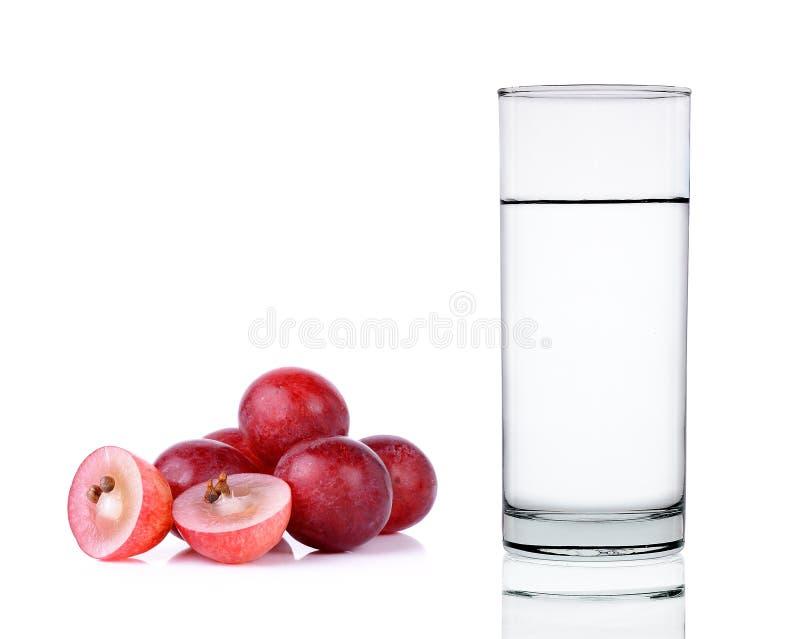 Water van glas met druif op de witte achtergrond wordt geïsoleerd die stock foto