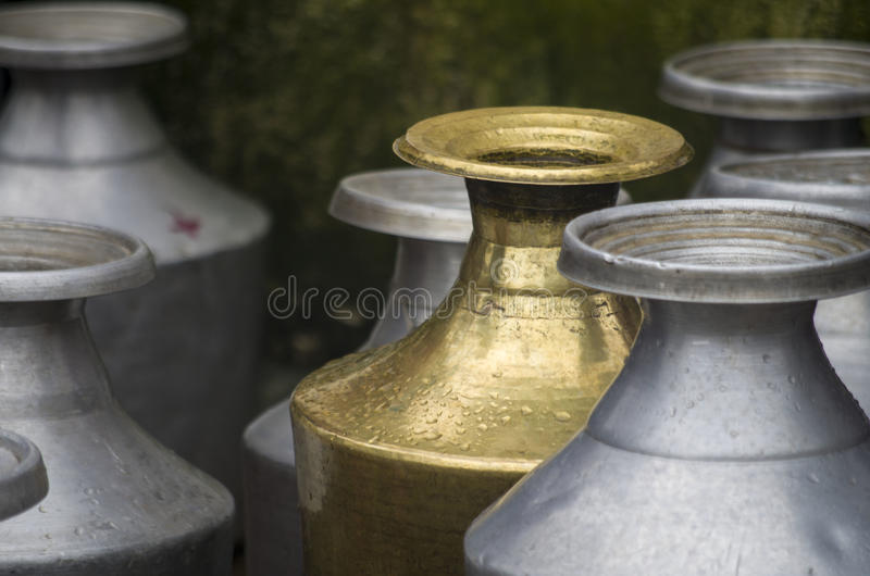 Water vessels. Traditional water vessels lined up to be filled with water in a community tap. These kinds of vessels are still popular and used to in most of the stock photo