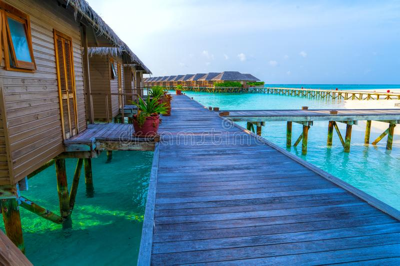 Wooden bridges leading to the huts on the shores of the tropical. Water Villas,Bungalows and wooden bridge at Tropical beach in the Maldives at summer day royalty free stock images