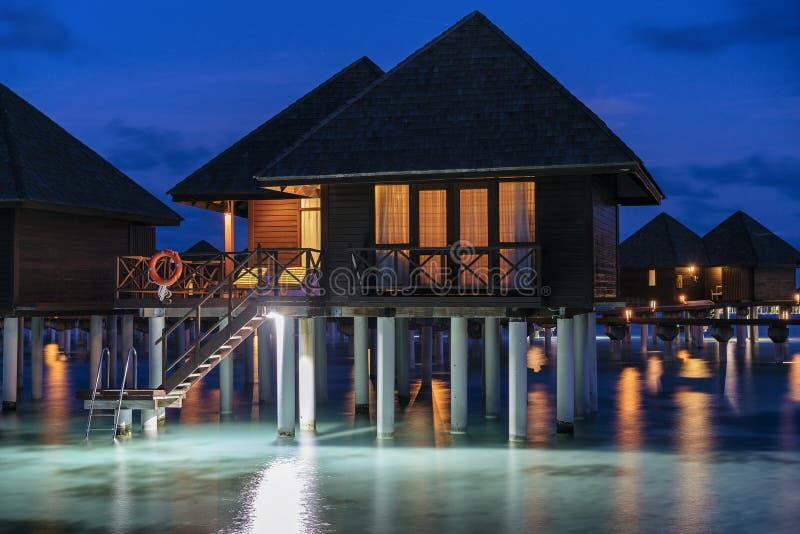 Water villas on Maldives resort island at night royalty free stock image