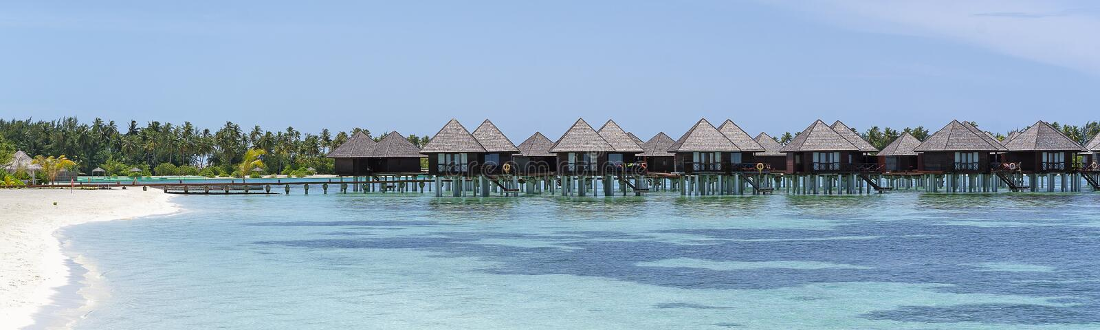 Water villas in Maldives in a sunny day, island paradise relax.  stock image