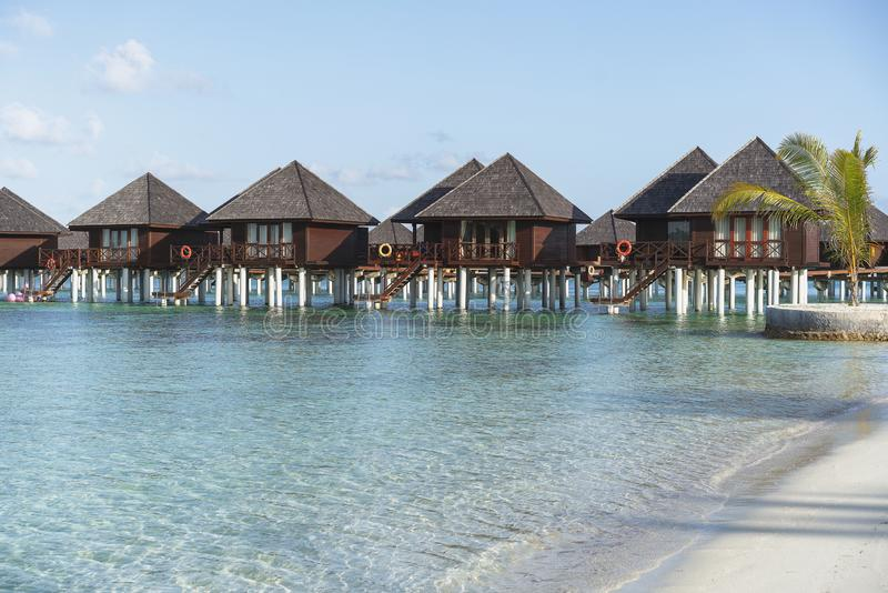 Water villas in Maldives in a sunny day, island paradise relax royalty free stock images