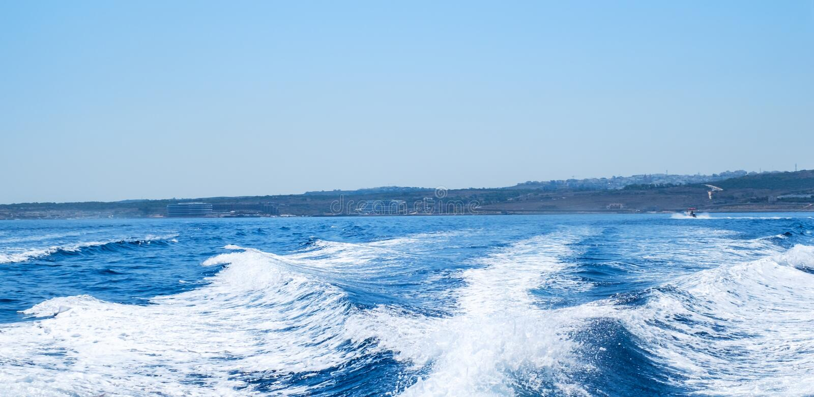 Water wake behind speed boat stock photography