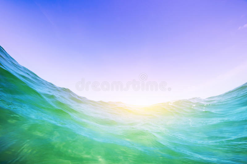 Water wave in the ocean. Underwater and blue sunny sky. Dynamic water wave in the ocean. View from the waterline. Underwater and blue sunny sky royalty free stock images