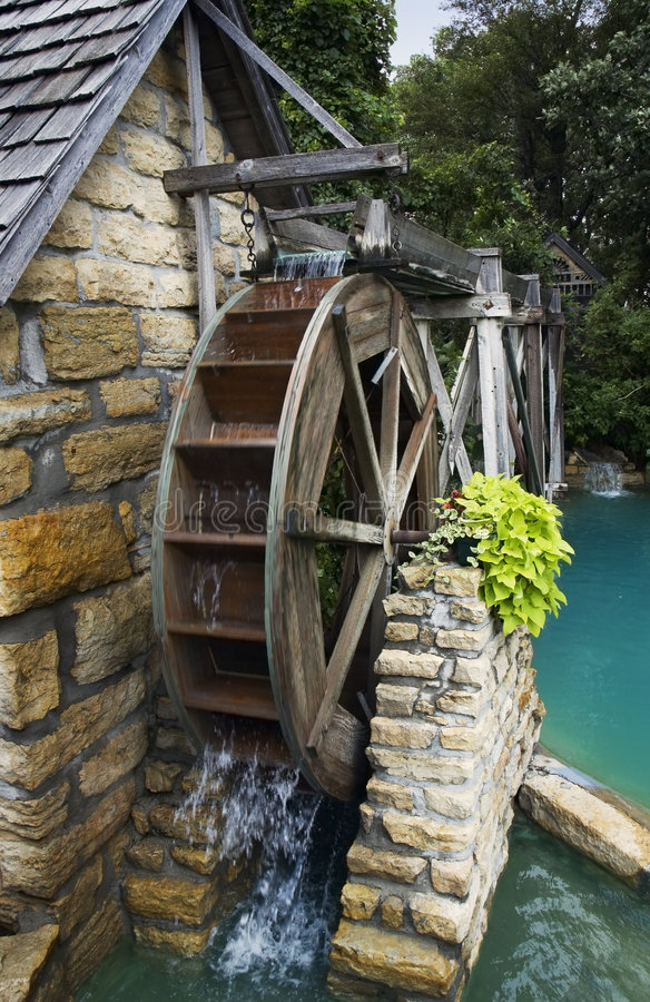 Water Wheel. Water flows over wheel of old wood and stone mill royalty free stock photos