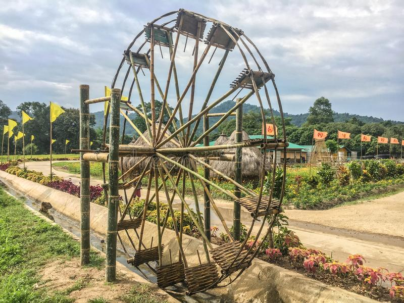 Water wheel is an essential agricultural tool that helps locals deliver water from the lower rivers or streams to the higher rice. Paddies for irrigation stock photography