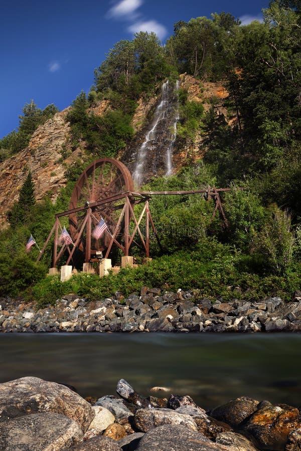 Water wheel and falls, Idaho Springs, Colorado. Waterwheel next to hillside waterfalls along rocky banks of river near Idaho Springs, Colorado with blue skies on stock image