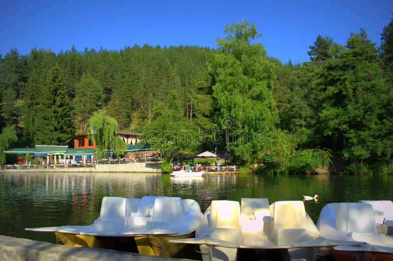 Water wheels in summer park pond. Pedalos waiting for tourists in Kleptuza lake in the most popular Bulgarian spa resort of Velingrad.It is the largest karst royalty free stock photo
