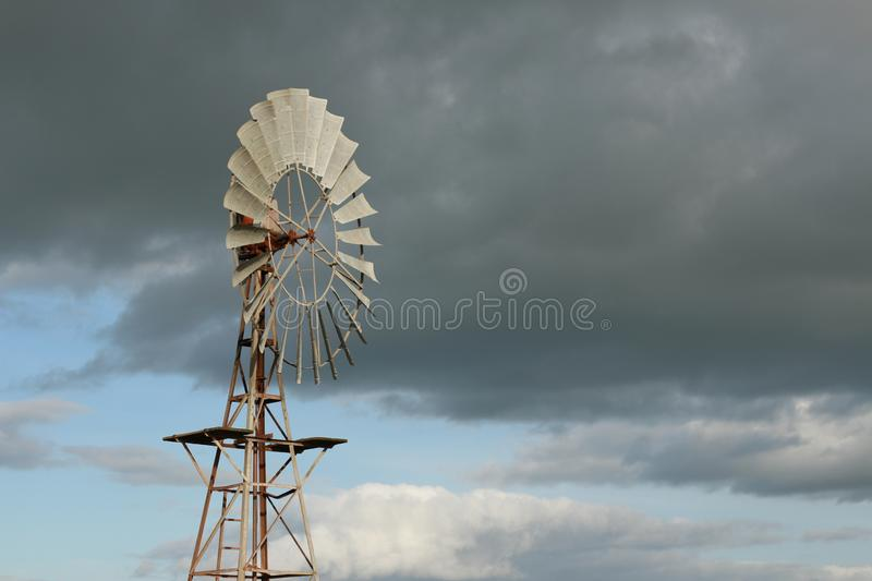 Water wind mill next to a large water storage tank on an agricultural sheep stock farm in rural Victoria with dark rain clouds in. The sky royalty free stock images
