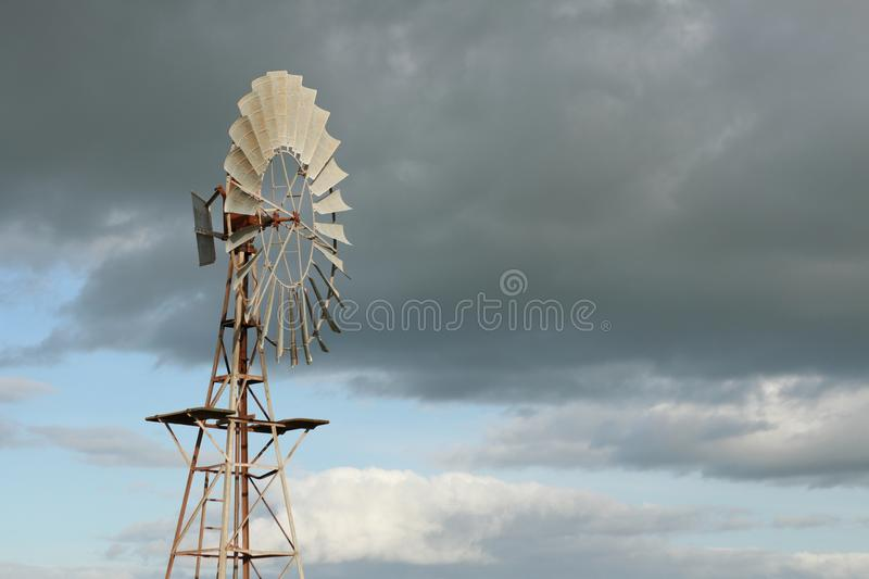 Water wind mill next to a large water storage tank on an agricultural sheep stock farm in rural Victoria with dark rain clouds in. The sky stock photography