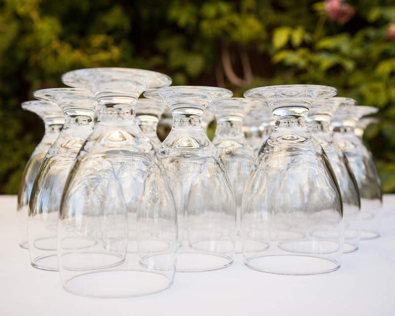 Water wine glasses lined up on a white table cloth. Table filled with upside down water wine glasses in a row royalty free stock images