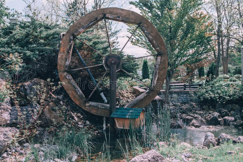 Water wooden old wheel mill in country village near pond stream. royalty free stock photography