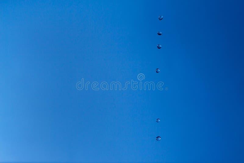 Waterbellen in de blauwe hemel De dalingen van het water op blauwe achtergrond Aqua, regen, weer, ontruimt Het leven, vrijheid, g stock afbeelding
