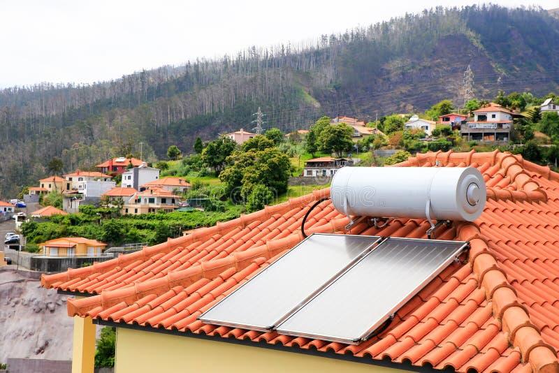 Waterboiler met zonnepanelen op dak van huis stock fotografie