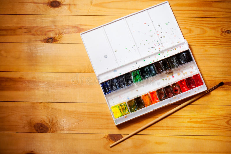 Watercolor aquarell paints in box with brush on wooden background royalty free stock image